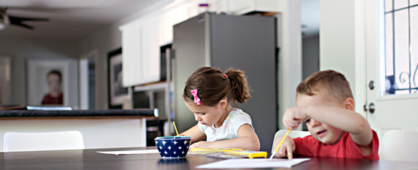 Two young children doing homework at dining room table.