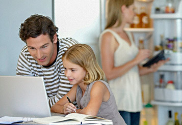 family looking at laptop in kitchen