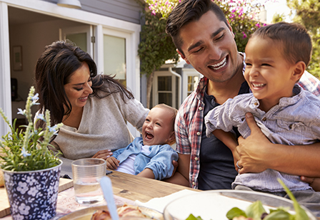 family laughing together at outdoor picnic table