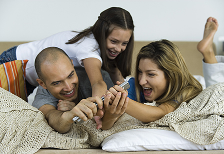 family of three wrestling over control of the remote
