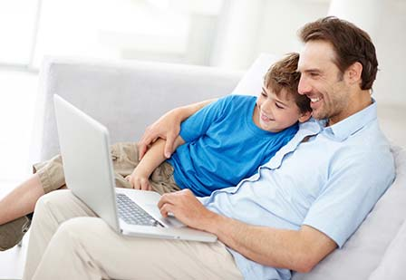 father and son looking at laptop together