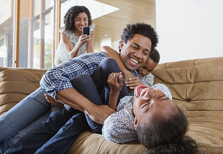 father laughing and playing with son and daughter on couch while their mother takes a photo of them on her smartphone