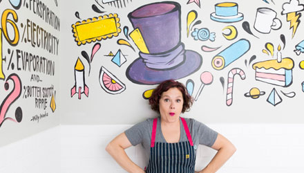 owner standing against a mural in her bake bar