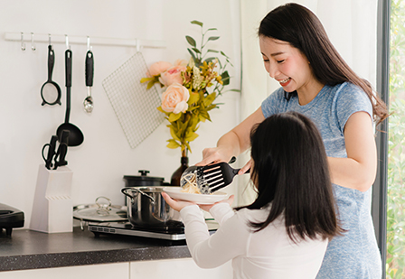 mother and daughter in a clean white kitchen preparing a meal