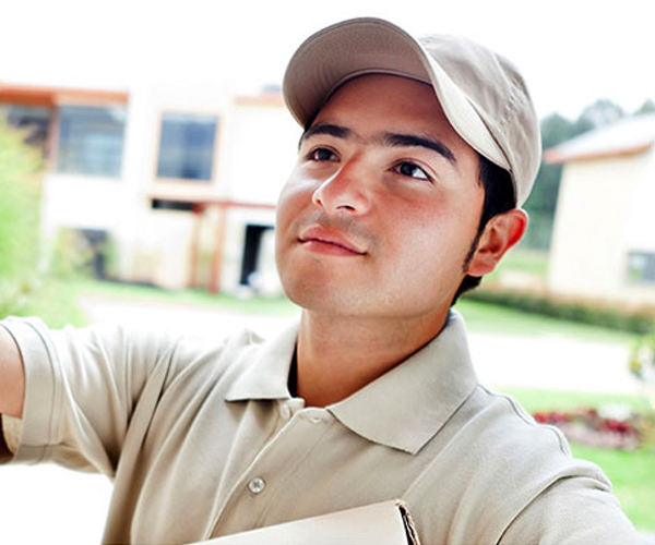 Front door image of a delivery man ringing doorbell.