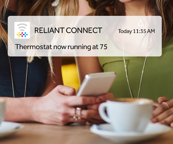 One middle aged woman showing another woman her thermostat setting inside Reliant connect app on smartphone.