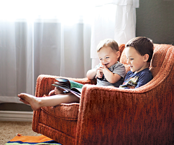 Two young boys sitting on a couch reading and laughing at a book.